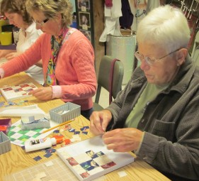 Everyone is concentrating on their geometric mosaics.