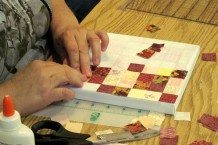 Carefully placing fabric tiles into place on the canvas.