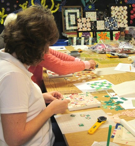 Working hard using the tools of the trade: design sketch, fabric, rotary cutter and mat, acrylic rulers, canvas, glue.