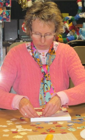 """Janet working on a geometric mosaic, surrounded by fabric """"tiles""""."""